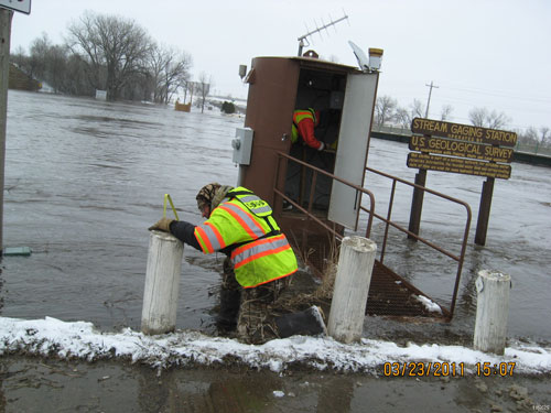 U.S. Geological Survey hydrologic technicians Tyler Meyer and Jesse Rigge document the river stage and ensure that the stream gauge on the James River at Huron, S. D., is working properly during high water in March 2011. Credit: USGS