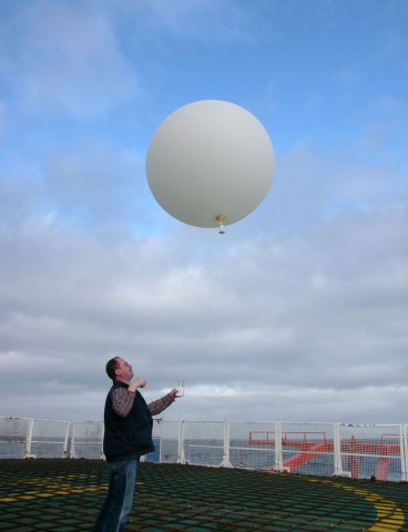 Release of a radiosonde, attached to a helium-filled balloon, on the helicopter deck of the research vessel Polarstern. The radiosonde seen here measured temperatures, wind speeds and ozone concentrations along a profile up to an altitude of 20 kilometers. Credit: Hannes Grobe, CC BY-SA 2.5