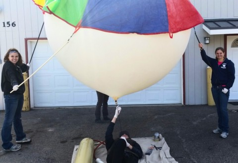 Amelia Yarborough, 18 (left), and Jamie Shultz, 17 (right), secure the balloon while Jordan Herbst, 16 (bottom), fills it with helium. Credit: Tony Phillips