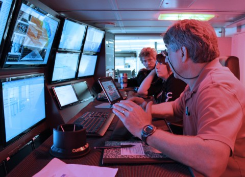 Team members on watch stand in the R/V Falkor's science control lab, where the monitors display real-time multibeam, magnetometer, and gravimeter data streams.Watch standers are responsible for monitoring and logging the quality of the incoming data, communicating with the bridge if course and speed adjustments are warranted, transmitting data to the processing computers in the adjoining room, and conducting sound velocity profiles. Credit: Daniel Wagner
