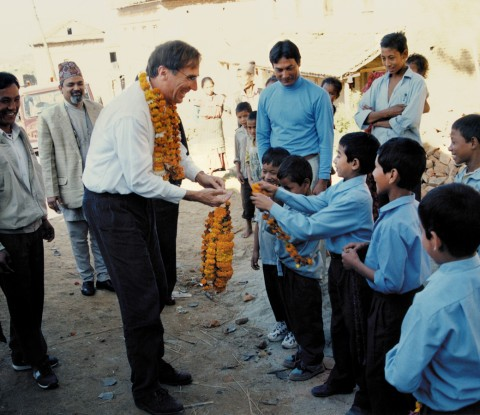 Children giving garlands to Brian Tucker at the inauguration of the school in the village of Nanghkeh in Nepal's Kathmandu Valley. The school was retrofitted in 1998 through a joint project of GeoHazards International and Nepal's National Society for Earthquake Technology. Credit: NSET