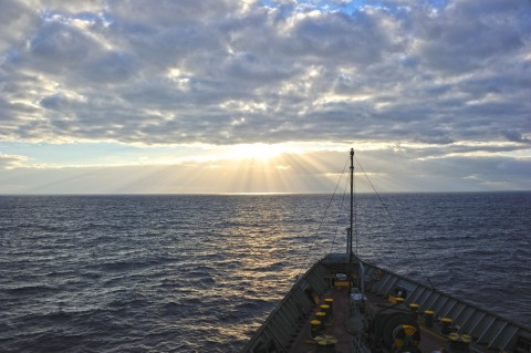 Heavy cloud layer darkens the sea off the bow of a cargo ship laden with instruments used to collect data on the stratocumulus-to-cumulus transition.  Credit: Ernie Lewis