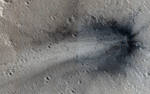 A recent impact on Elysium Planitia is visible in this image, as are the rays of dark subsurface material that the impact sprayed outward. The crater is on the order of tens of meters across. Credit: HiRISE