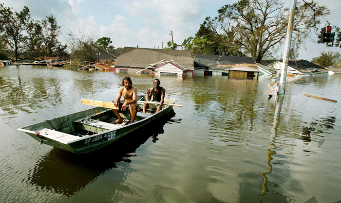 Two men paddle in high water in New Orleans' Ninth Ward on 31 August 2005 after Hurricane Katrina devastated the Gulf coast. Credit: Mario Tama/Getty Images