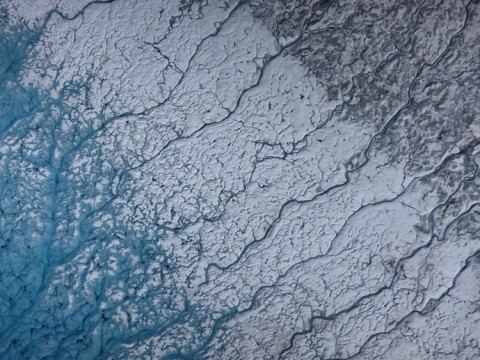 Aerial photograph taken on 24 July 2015 over the southwest portion of the Greenland ice sheet, near Kangerlussuaq. (left) The turquoise color is characteristic of meltwater on the shore of a supraglacial lake. (center) Area from which the lake water has receded, removing impurities and leaving bare ice. (right) Ice and snow covered by surface impurities. Credit: Marco Tedesco