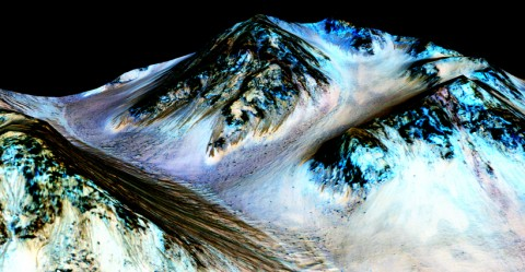 Dark, narrow streaks on Martian slopes such as these at Hale Crater are inferred to be formed by seasonal flow of water on contemporary Mars, according to NASA. The imaging and topographical information in this processed, false-color view come from the High Resolution Imaging Science Experiment camera on NASA's Mars Reconnaissance Orbiter (MRO). Planetary scientists using observations with the Compact Reconnaissance Imaging Spectrometer on the MRO detected hydrated salts on these slopes at Hale Crater, corroborating the hypothesis that the streaks are formed by briny liquid water. Credit: NASA/JPL-Caltech/Univ. of Arizona