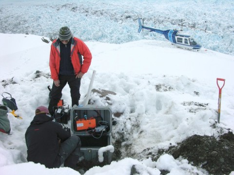Researchers retrieve data from a seismometer adjacent to Yahtse Glacier. At this ocean-terminating glacier, measurements of background seismic noise revealed how water flow becomes more efficient over the course of a summer. Credit: Timothy Bartholomaus