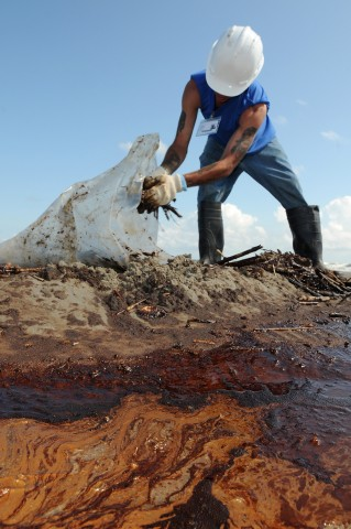 A contract worker from Health, Safety, and the Environment (HSE) loads oily waste onto a trailer on Elmer's Island, just west of Grand Isle, La., 21 May 2010 during the BP Deepwater Horizon oil spill. Credit: Patrick Kelley, U.S. Coast Guard/Marine Photobank