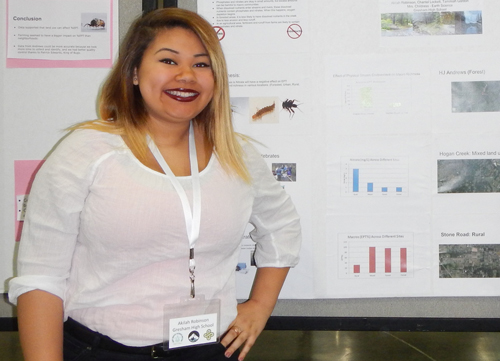 """Cascades-to-Coast GK–12 student Akilah Robinson (Gresham High School, now graduated) stands in front of her poster on insects that live in streams, entitled """"How does Nitrate Affect Macroinvertebrate Communities,"""" at the 2014 Joint Aquatic Science Conference."""