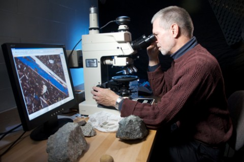 Robert Hazen studies thin slices of rock under a microscope in his lab at the Carnegie Institution in Washington, D. C.