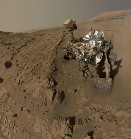 """Fig. 1. Curiosity used its arm-mounted camera to take dozens of images at a sandstone drill target called Windjana that were combined into this """"selfie."""" The view does not include the rover's arm. Most of the frames of this mosaic view were taken during the 613th Martian day, or sol, after landing (27 April 2014). Frames showing Windjana after completion of the drilling were taken on sol 627 (12 May 2014). Aeolis Mons can be seen in the background. Credit: NASA/JPL-Caltech/MSSS."""