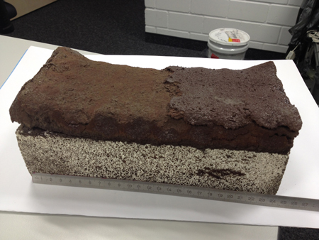 A red-brown brick made from simulated lunar soil sits atop a supporting block. Researchers made the 24-centimeter-long brick by sintering a simulant of Moon soil with a beam of concentrated sunlight. Credit: Alexandre Meurisse
