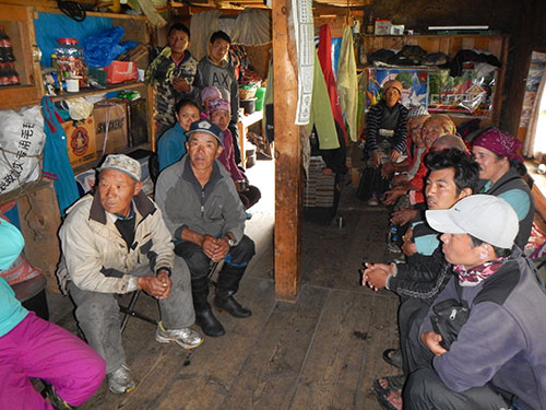 Community members below Tsho Rolpa glacial lake discuss damage from an earthquake.