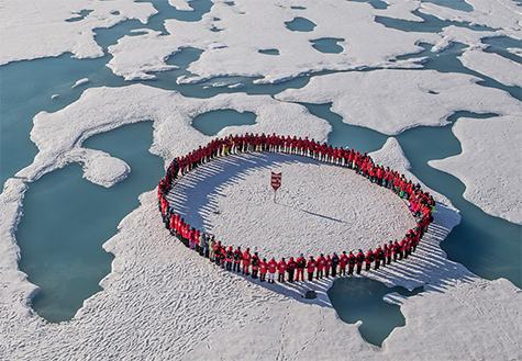 """Citizen scientists take a moment to stand &334;at the top of the world"""" as they encircle the North Pole. Credit: Lauren Farmer"""