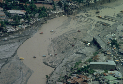 Cars and people traverse a flooded river in June 1991 after lahars wiped out bridges.