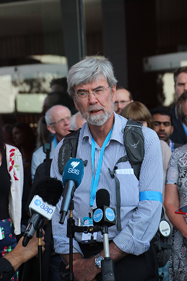 John Church gives a media interview as a part of a lunchtime protest at a climate science conference in Melbourne.