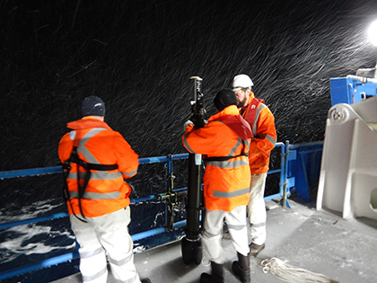 Three crew members prepare a profiling float for launch near the ice edge in the Southern Ocean.