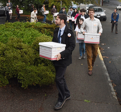 Washington state carbon tax ballot supporters carry signatures to a state elections office.