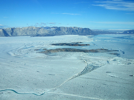 Aerial view, looking north over the front of Nioghalvfjerdsbræ (79°30'N, 19°30'W). Nioghalvfjerdsbræ and its southern neighbor, Zachariae Isstrøm, form the major outlet glaciers of the Northeast Greenland Ice Stream. Credit: Mirko Scheinert