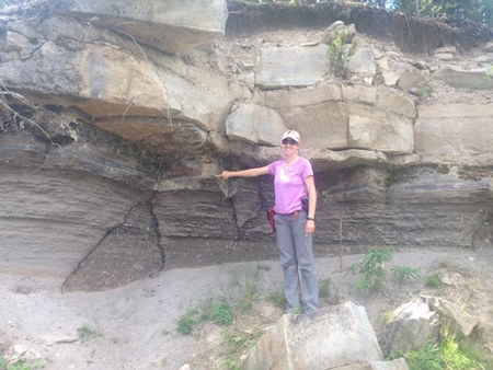 Christy Till points at an ash layer in the Lava Creek tuff, which deposited during Yellowstone's most recent supereruption.