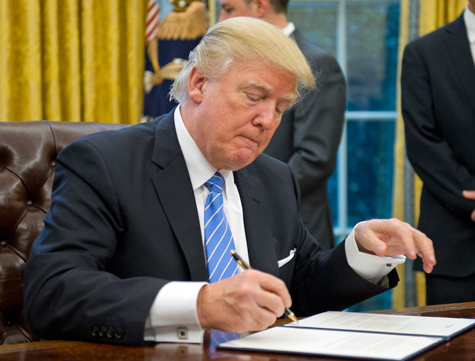 President Donald Trump signed three executive orders, including the hiring freeze, on 23 January.