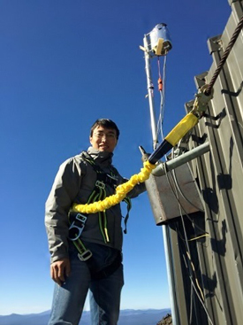 Researcher Lei Zhang wears a harness to access equipment at the Mount Bachelor Observatory.