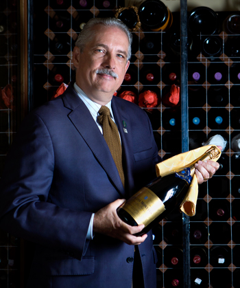 Tony Busalacchi, a certified sommelier, holds a bottle of wine in the wine cellar at his former Maryland residence.