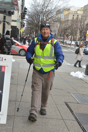 """Rick Spinrad strides through downtown Washington, D. C., on his """"long walk home"""" from Cape Henlopen, Del., to Newport, Ore."""