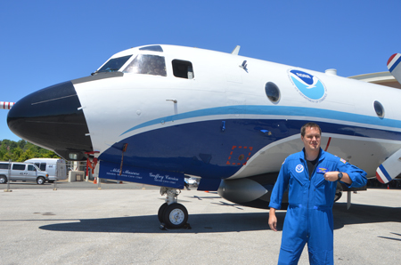 "Lt. Danny Rees, a pilot with the NOAA Commissioned Officer Corps, stands before a NOAA Lockheed WP-3D Orion ""Hurricane Hunter"" airplane."
