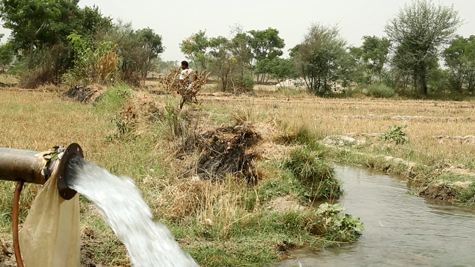 Groundwater fills an irrigation ditch as a Pakistani farmer prepares his field for cotton planting.