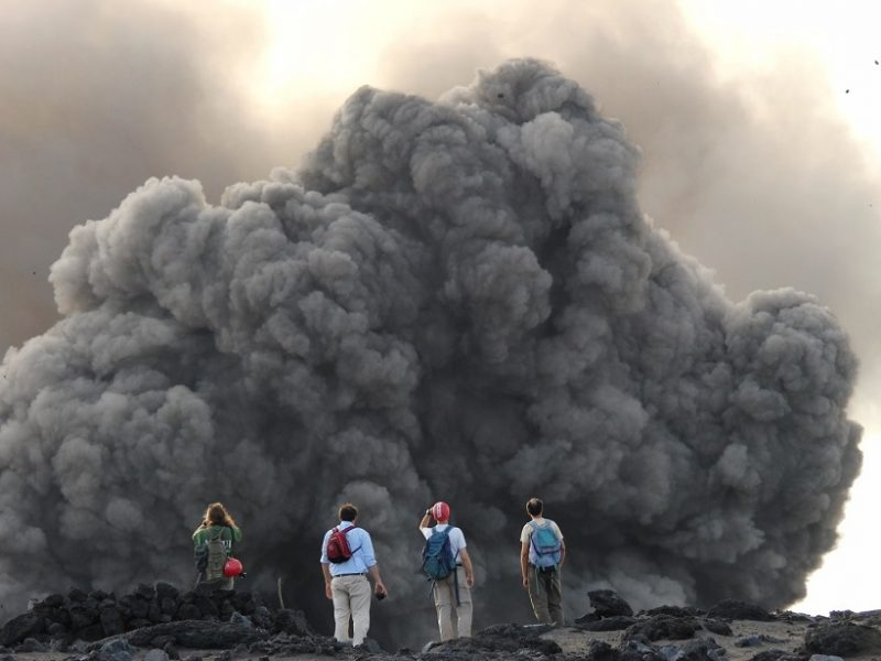Researchers in front of a volcanic explosion at Yasur volcano in Vanuatu, which is ejecting volcanic ballistic projectiles and a small ash plume. Photo: AGU's Eos/Marco Albano