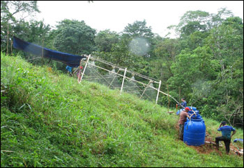 A sprinkler simulates rainfall at a steeply sloped field site in the forests of Panama