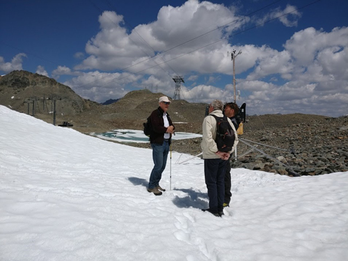 Glaciologist Hans Oerlemans shows a television reporter and cameraman around on a small artificial glacier he created near Diavolezza, Switzerland.