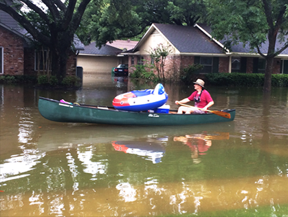 A friend navigates a canoe laden with pets and supplies through floodwaters in Houston on 27 August.