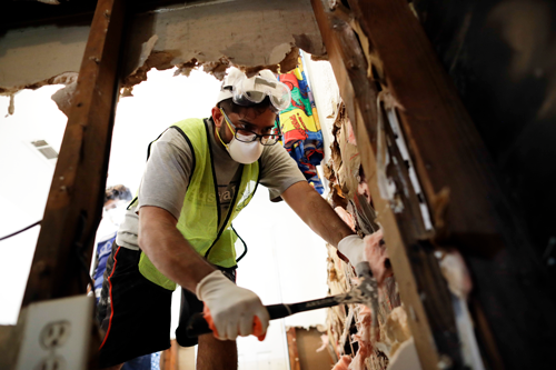 A volunteer removes sodden drywall and insulation at a Houston home flooded by Harvey
