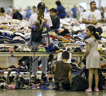 Children evacuated from Harvey's floodwaters look through donated shoes at a shelter in downtown Houston on 30 August.