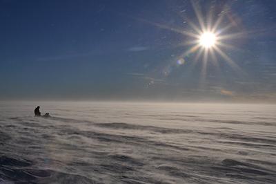 Operator prepares an ice-sounding radar during windy weather on Pine Island Glacier.