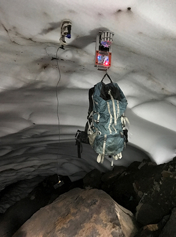"Two prototype robotic ""hands"" grip an ice cave's ceiling."