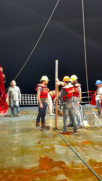Participants on the UNOLS Chief Scientist Training Cruise retrieve a sediment core.