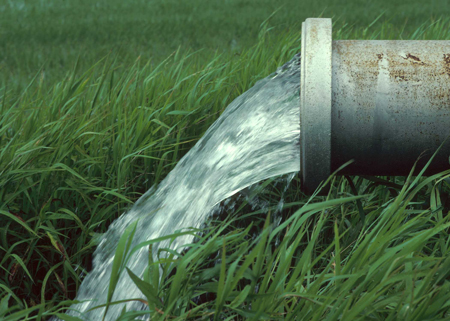 A water supply system releasing water into a field.