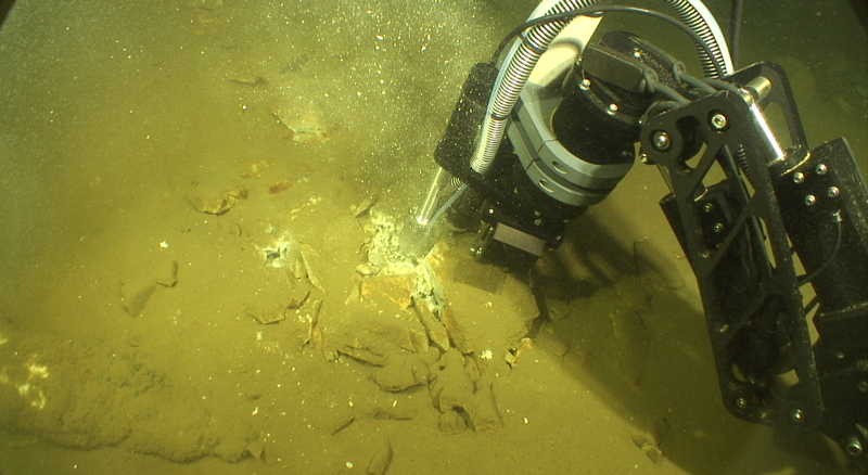The manipulator arm of ROV Yogi deploys equipment to acquire gastight fluid samples from a Yellowstone Lake floor vent.