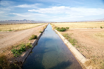 An irrigation ditch brings water to farms in California; around it stretches dusty desert