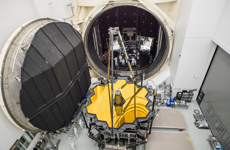 Engineers pose with the James Webb Space Telescope