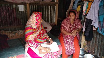 A project team member interviews a female head of household in an urban Dhaka slum.