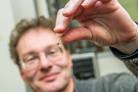 Oliver Tschauner holds a small piece of one of the diamond samples tested during the experiments