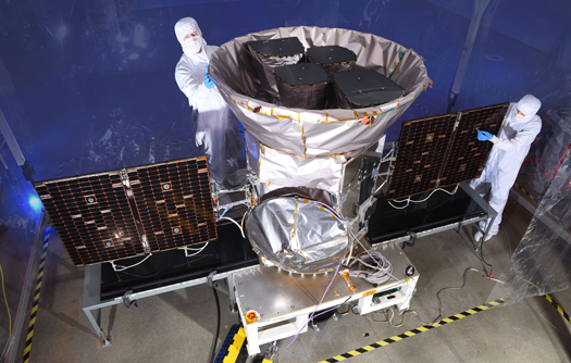 NASA engineers stand next to TESS during its final testing stages at Kennedy Space Center in Florida.