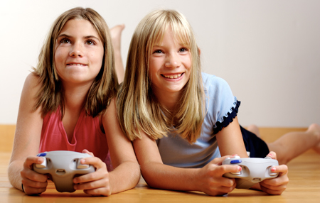 Two girls lie on their stomachs on the floor, holding video game controllers and looking up.
