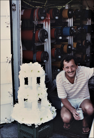 Newlywed Batiza kneels next to his wedding cake, which had survived a small smashup on its transit to the East Pacific Rise.