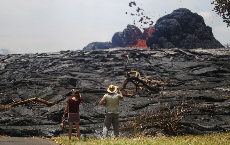 Lava erupts from a fissure in the Leilani Estates subdivision on May 24 as bystanders look on.