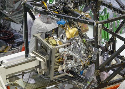 Engineers installing the MIRI instrument in JWST's instrument module.